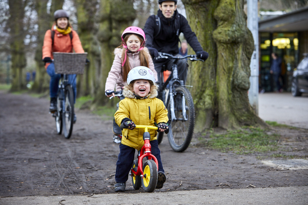 Small child on balance bike with their family