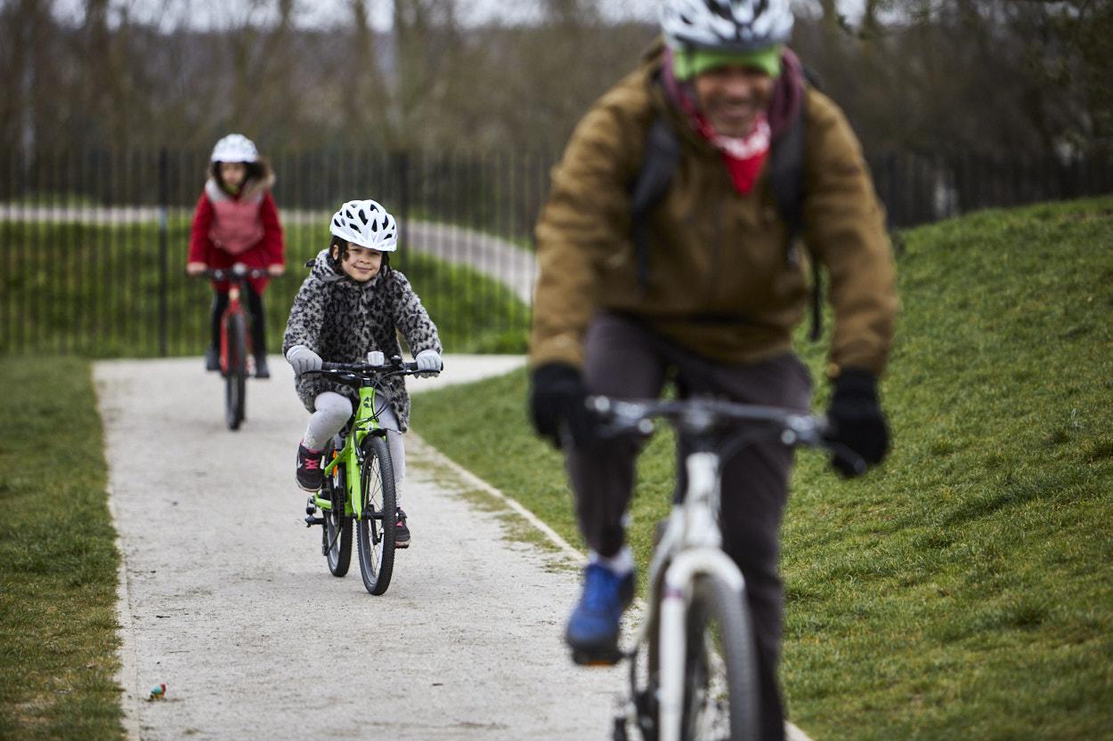 Family cycling across park