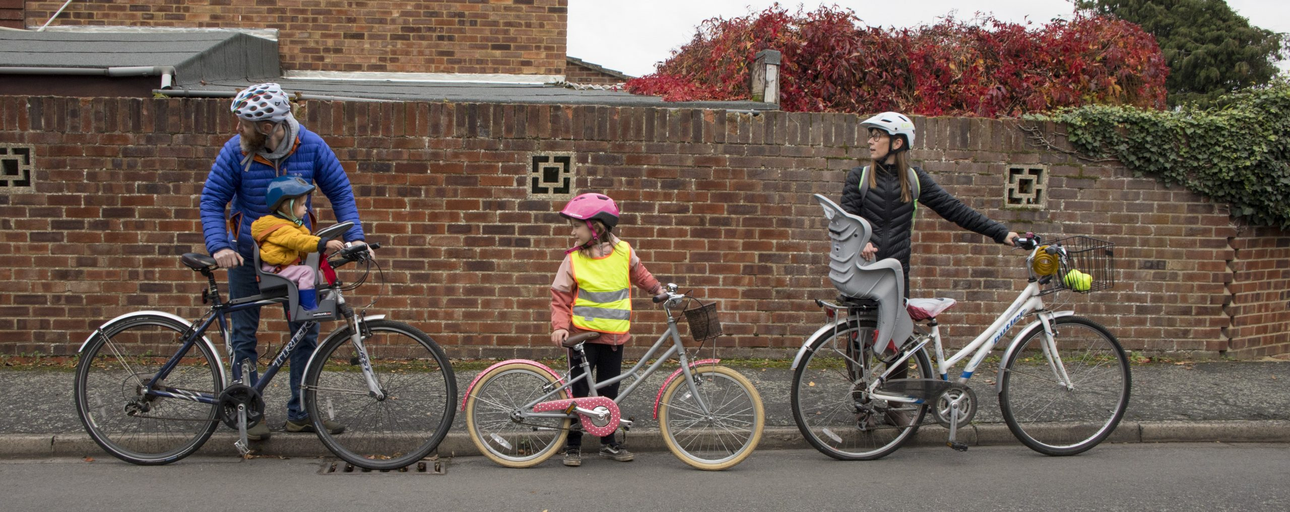 A man, child and woman stood next to their bikes looking behind them. The man has a toddler in a seat on his bike.
