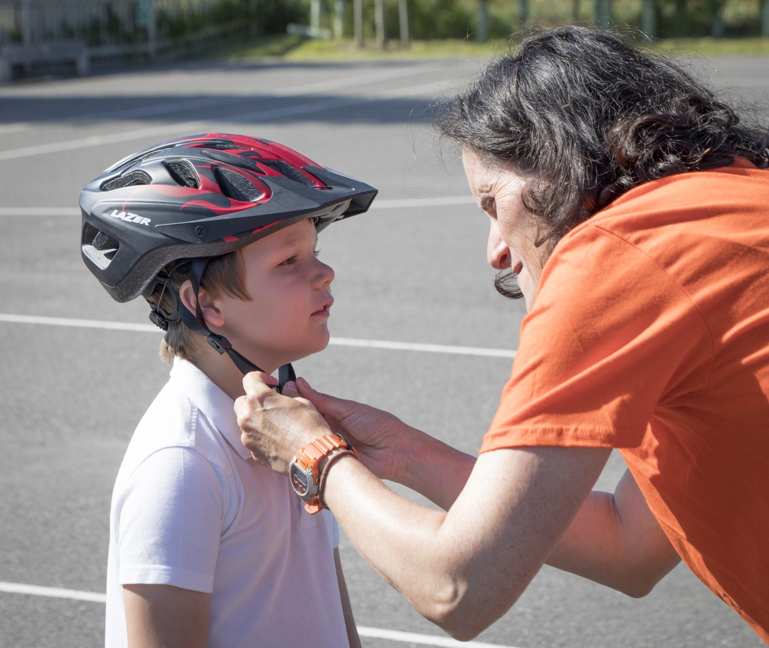 A woman puts a cycle helmet on a boy