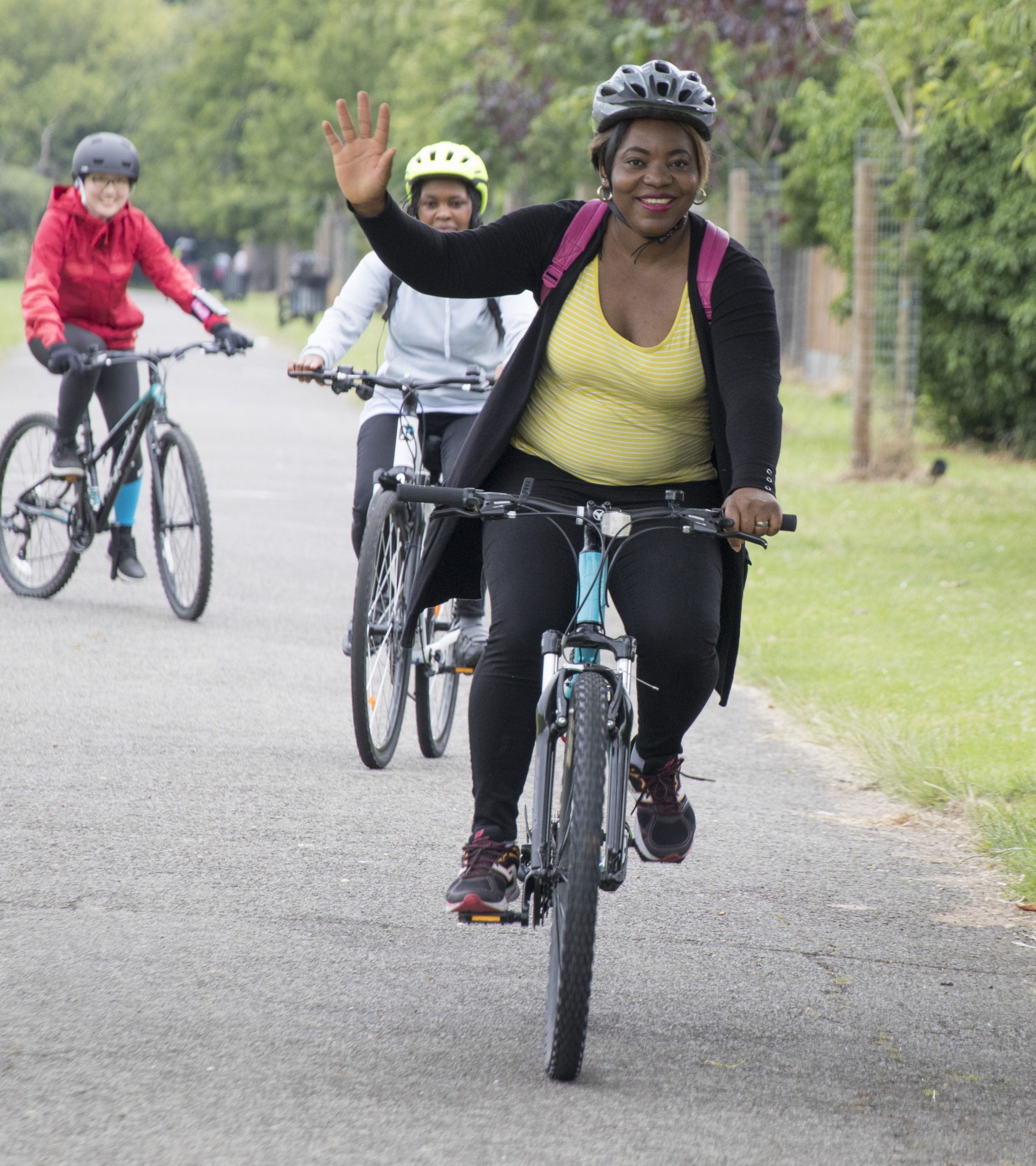 A woman waves at the camera whilst riding a bike