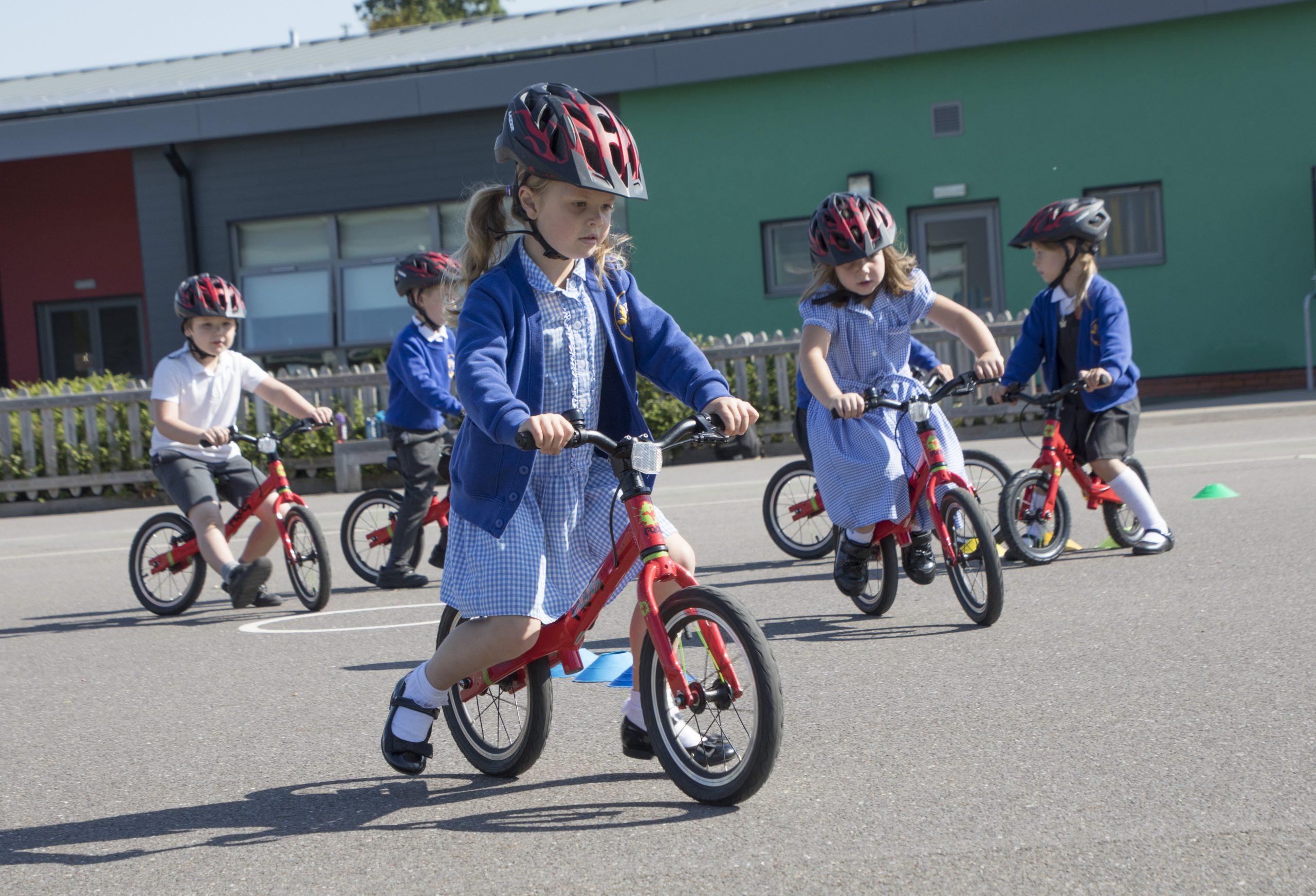 Young children in school uniform riding balance bikes