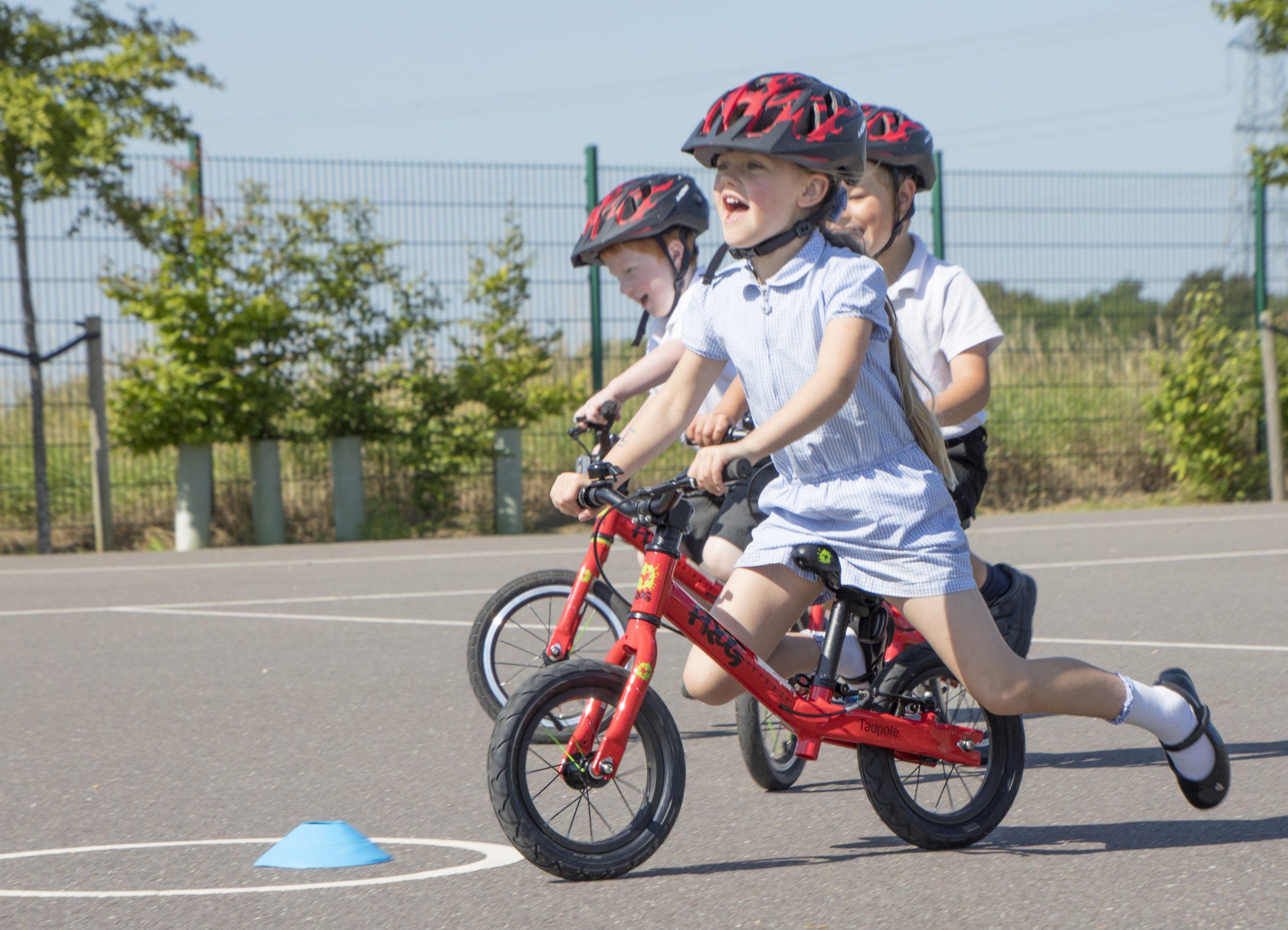 A young girl rides a balance bike