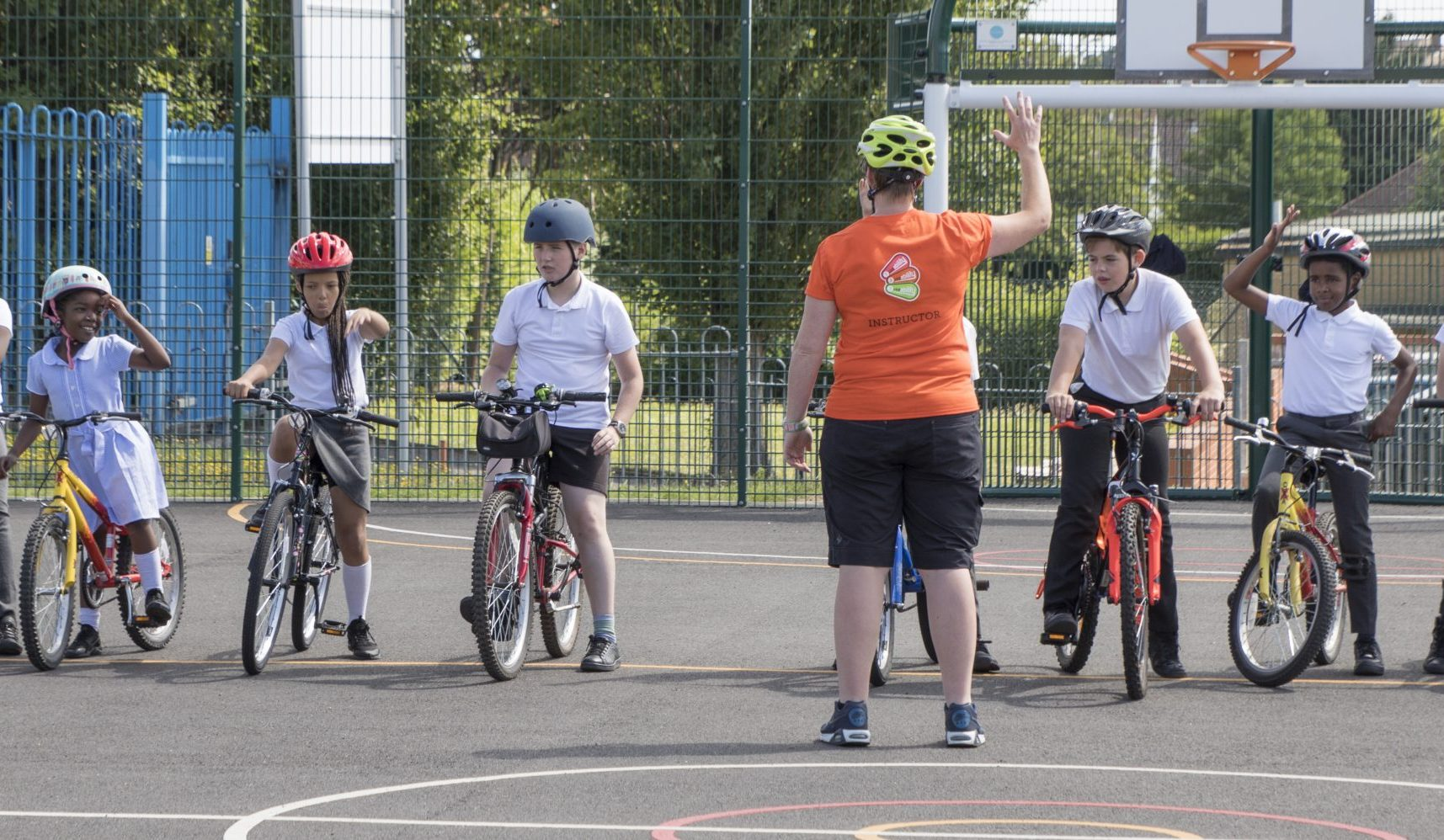 An instructor in front of a line of children on bikes