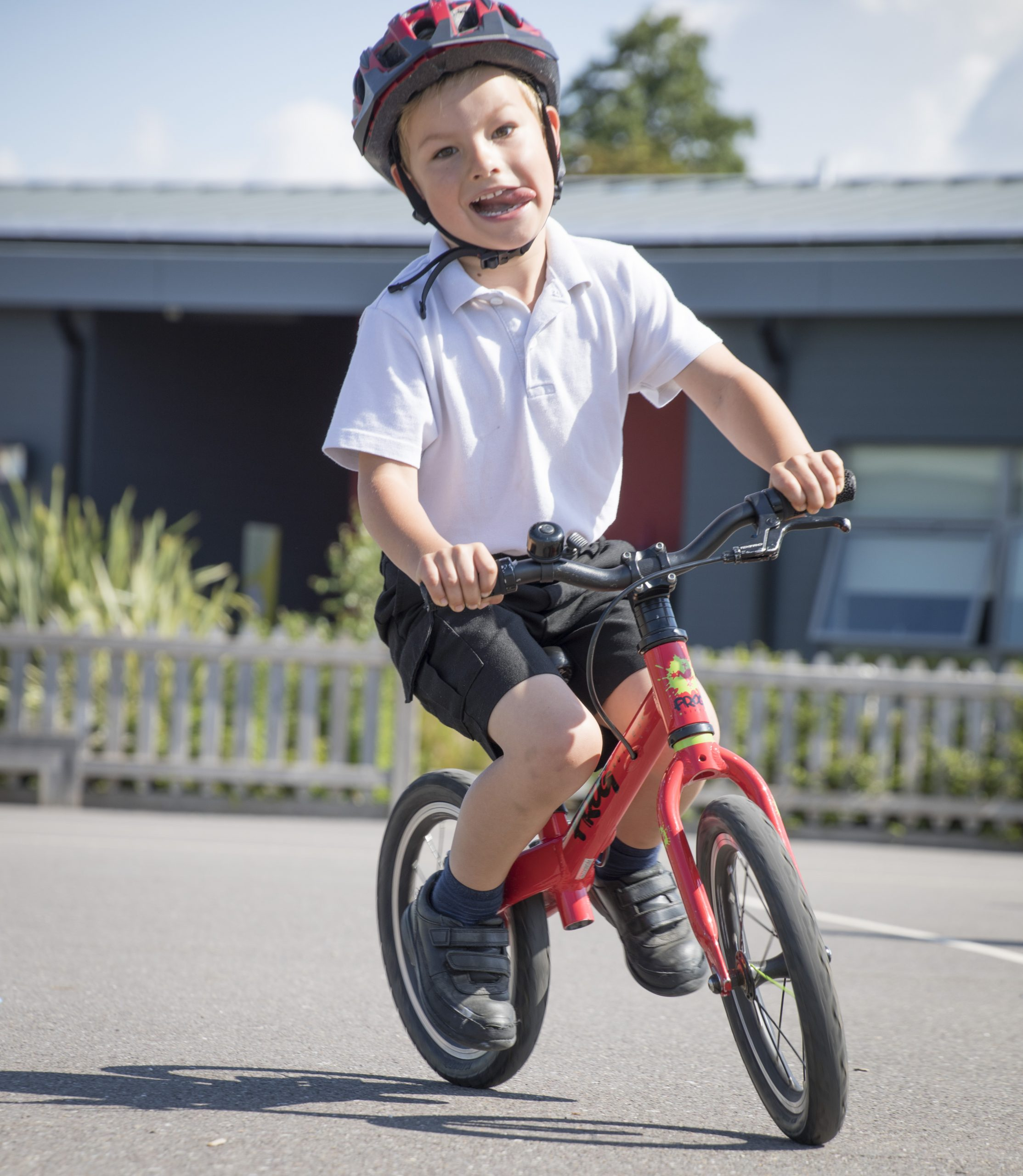 Small boy on a bike sticking his tongue out