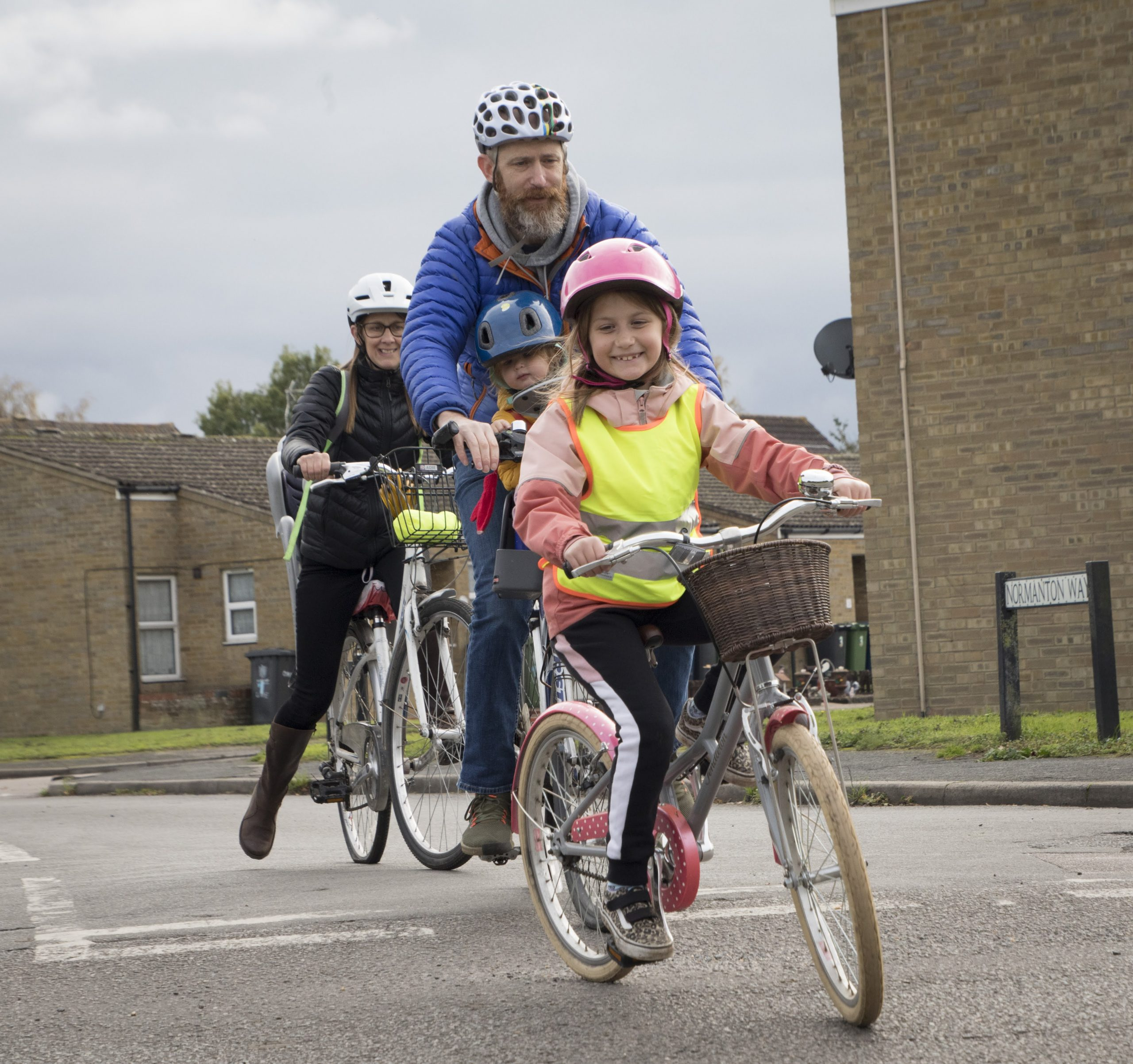 A young girl smiling on a bike with her dad and mum behind her on bikes