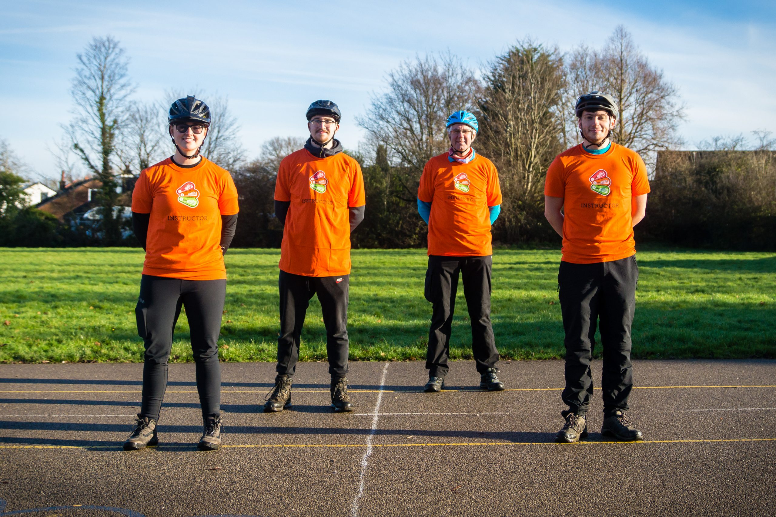 One female and three male Bikeability instructors stood in a line wearing orange t shirts