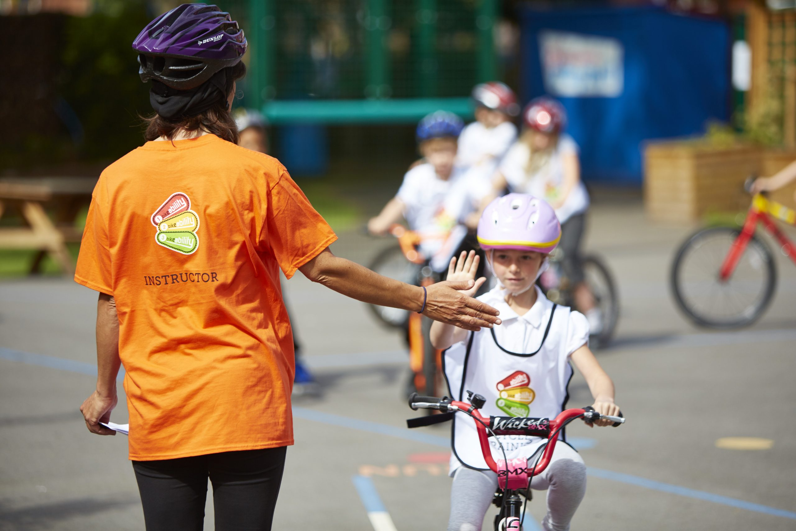 A Bikeability Professionals instructor high fiving a young girl on a bike