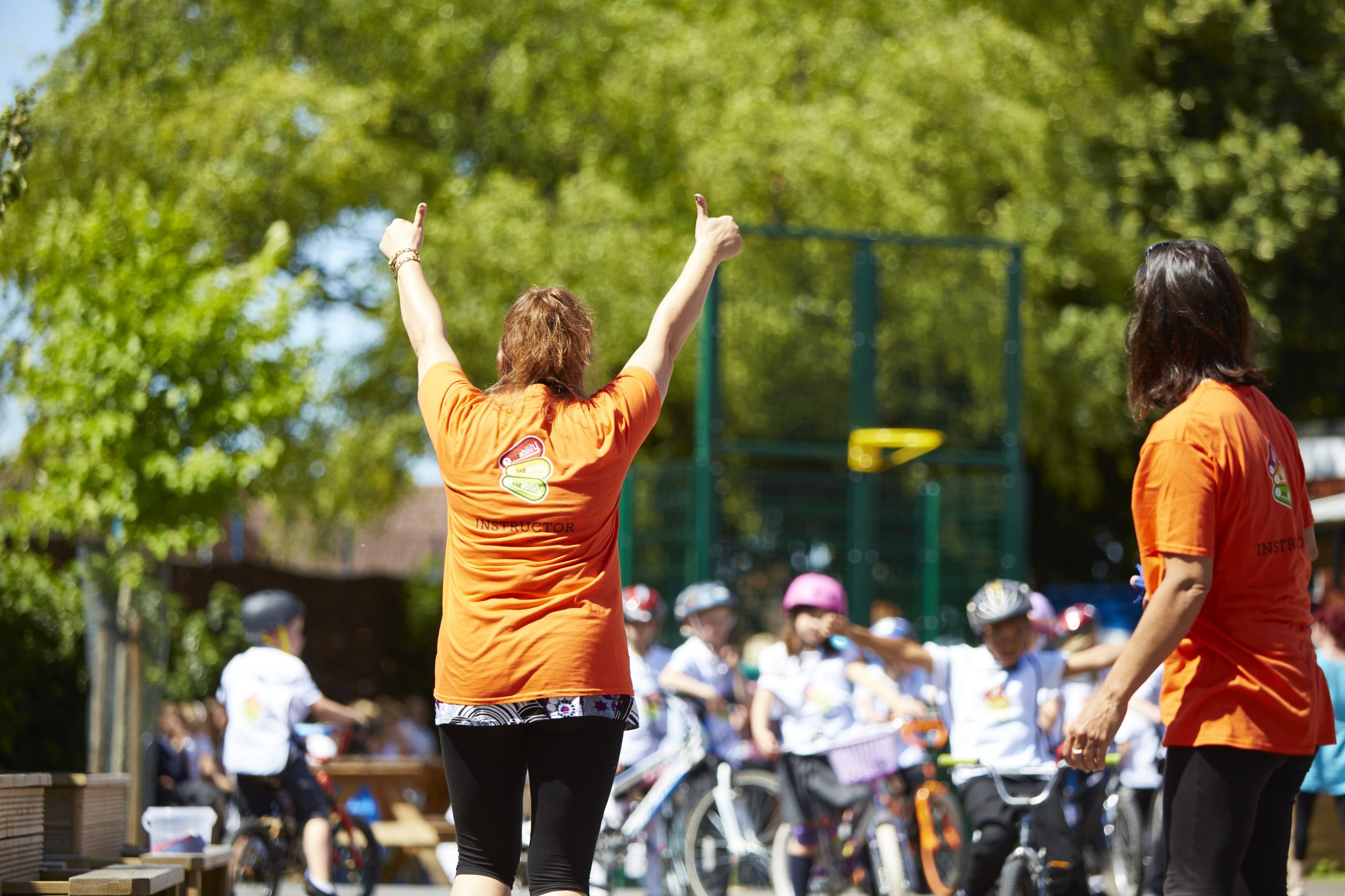 A Bikeability instructor with her back to the camera doing two thumbs up in the air