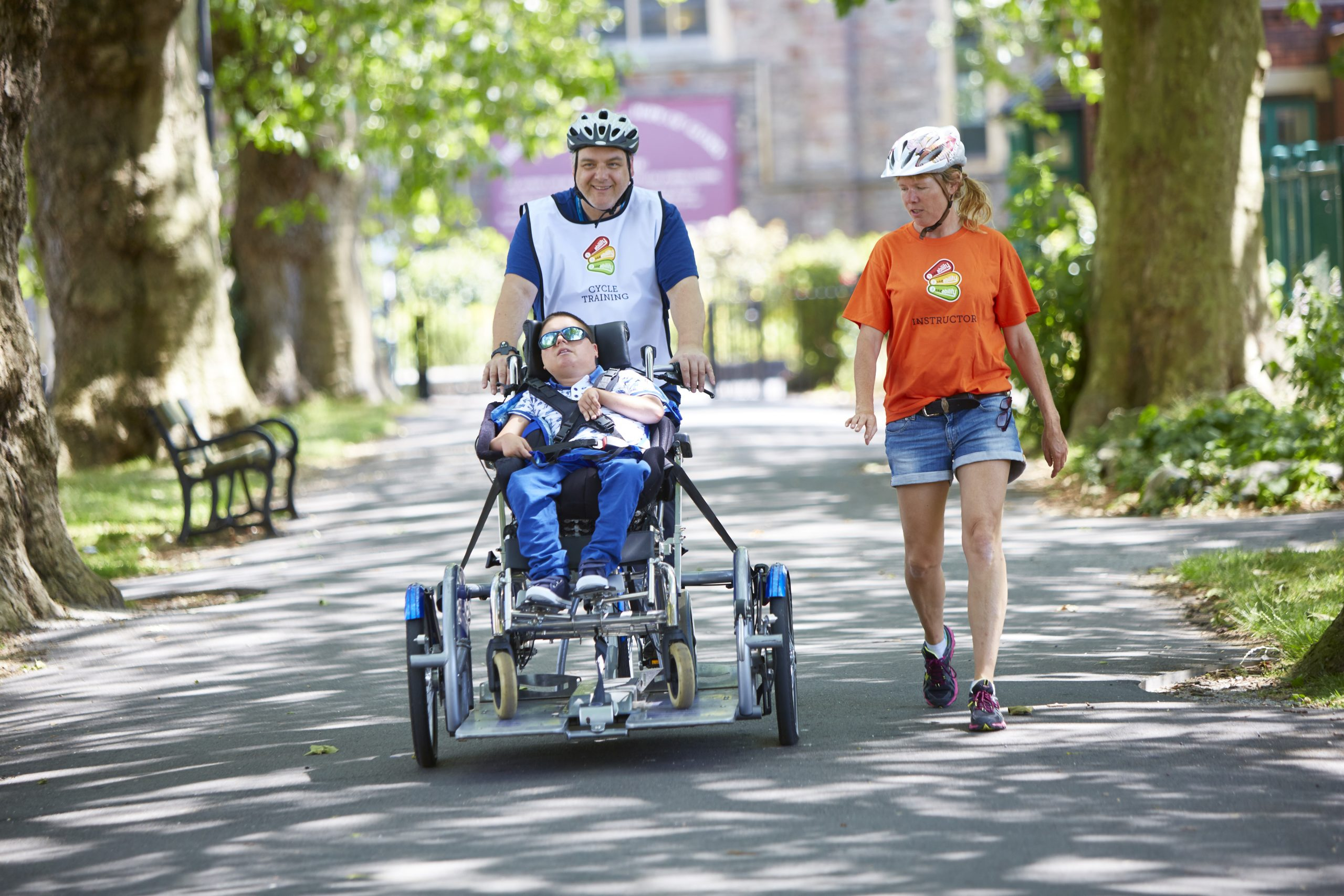 A child on an adapted bike being ridden by a man with a female instructor walking beside them
