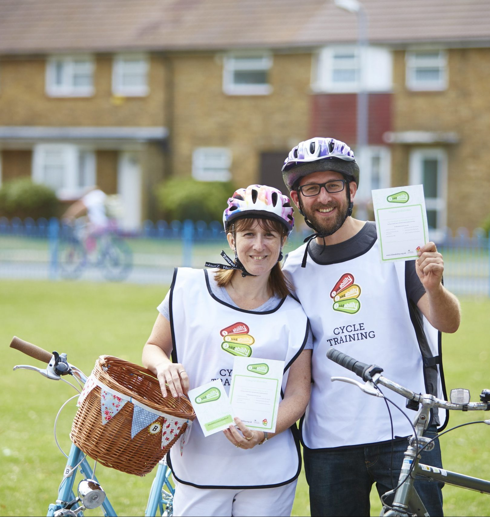 A man and a woman holding Bikeability certificates