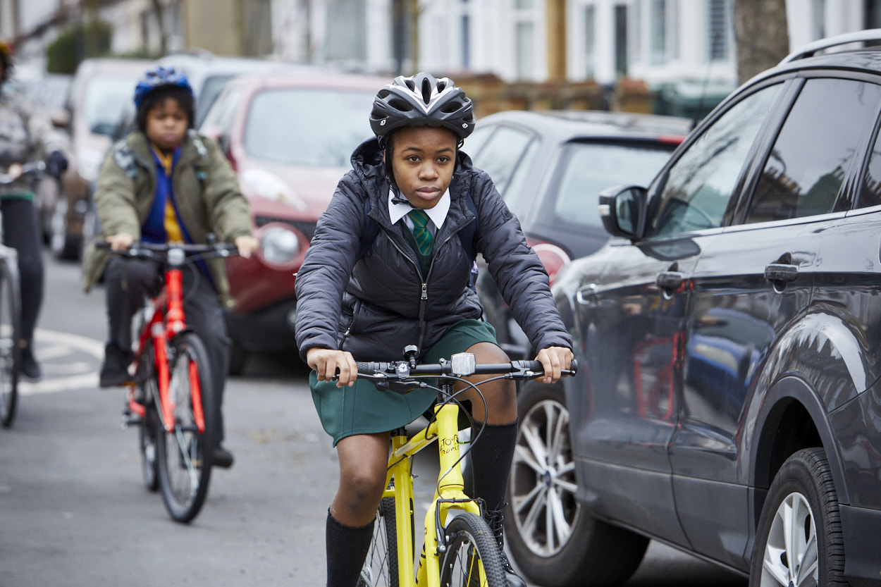 A girl cycles next to a car