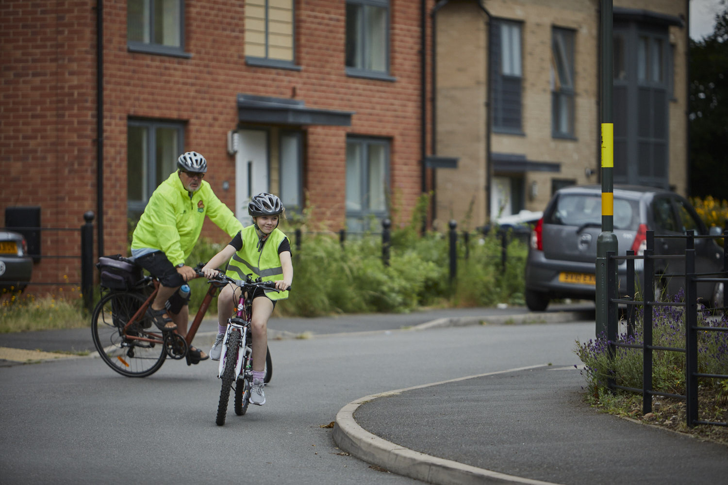 Young girl on bike in high vis with Bikeability instructor behind her