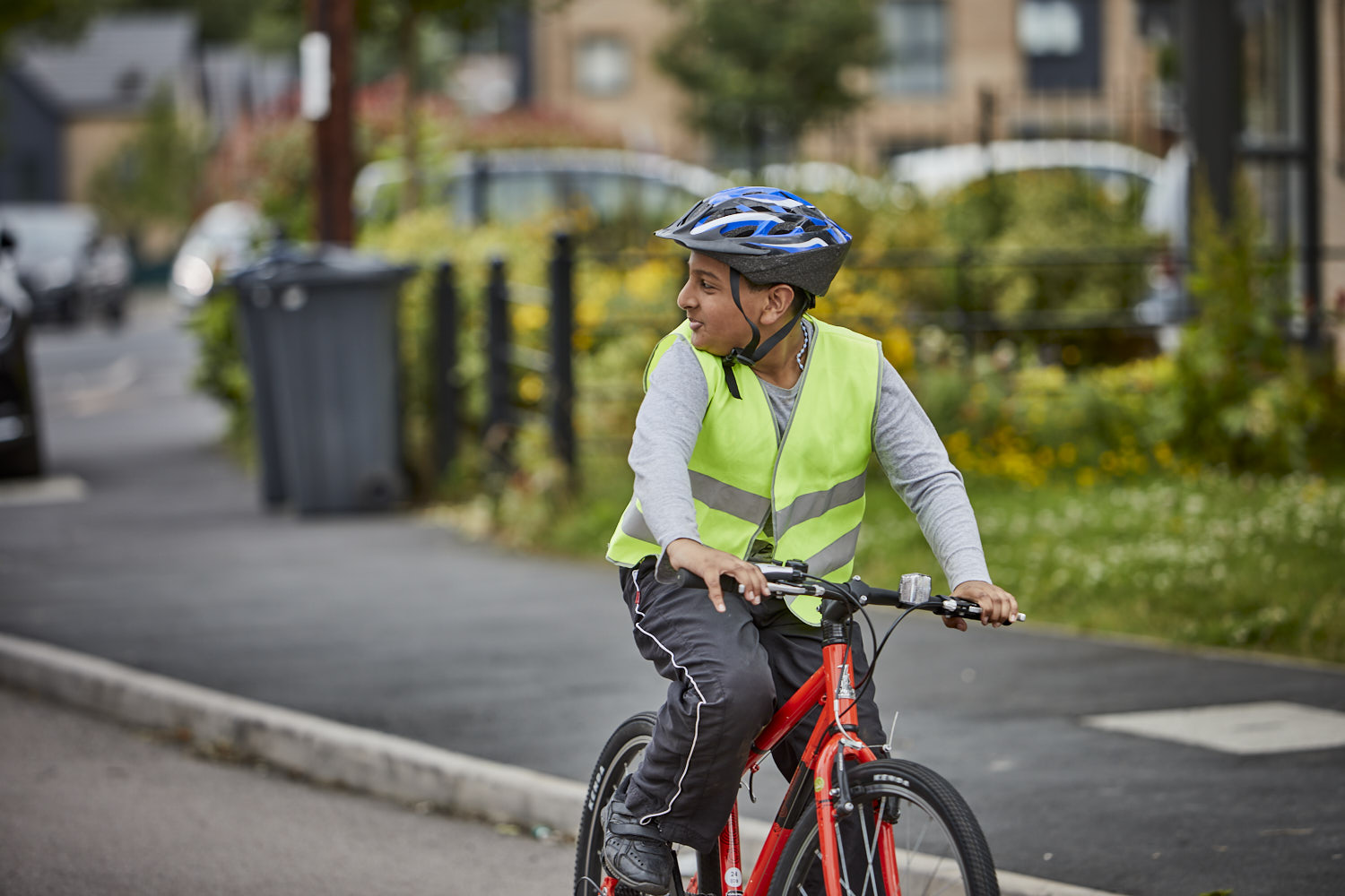 Young boy on a bike checking for cars behind him