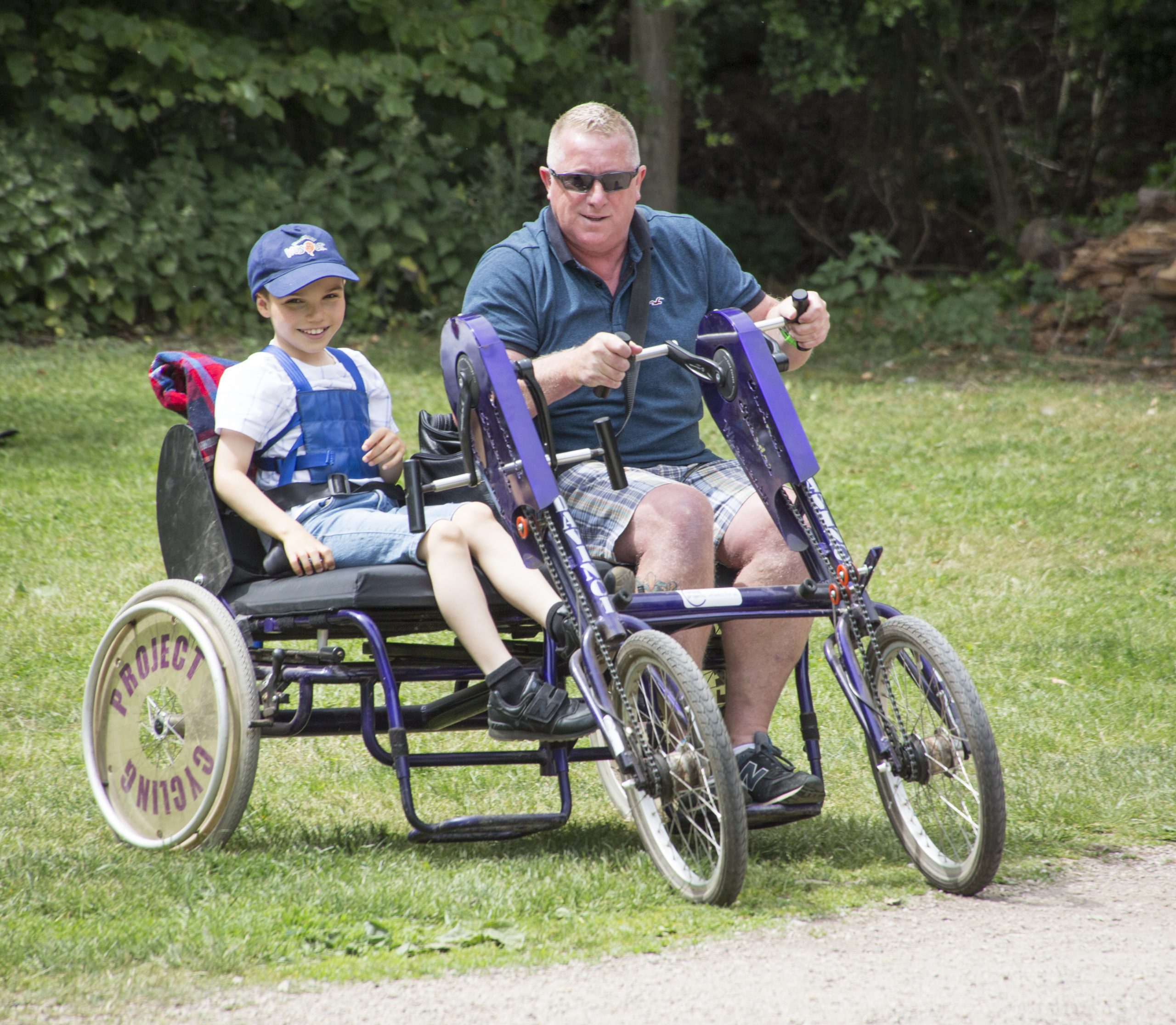 A child and man on a side by side bike