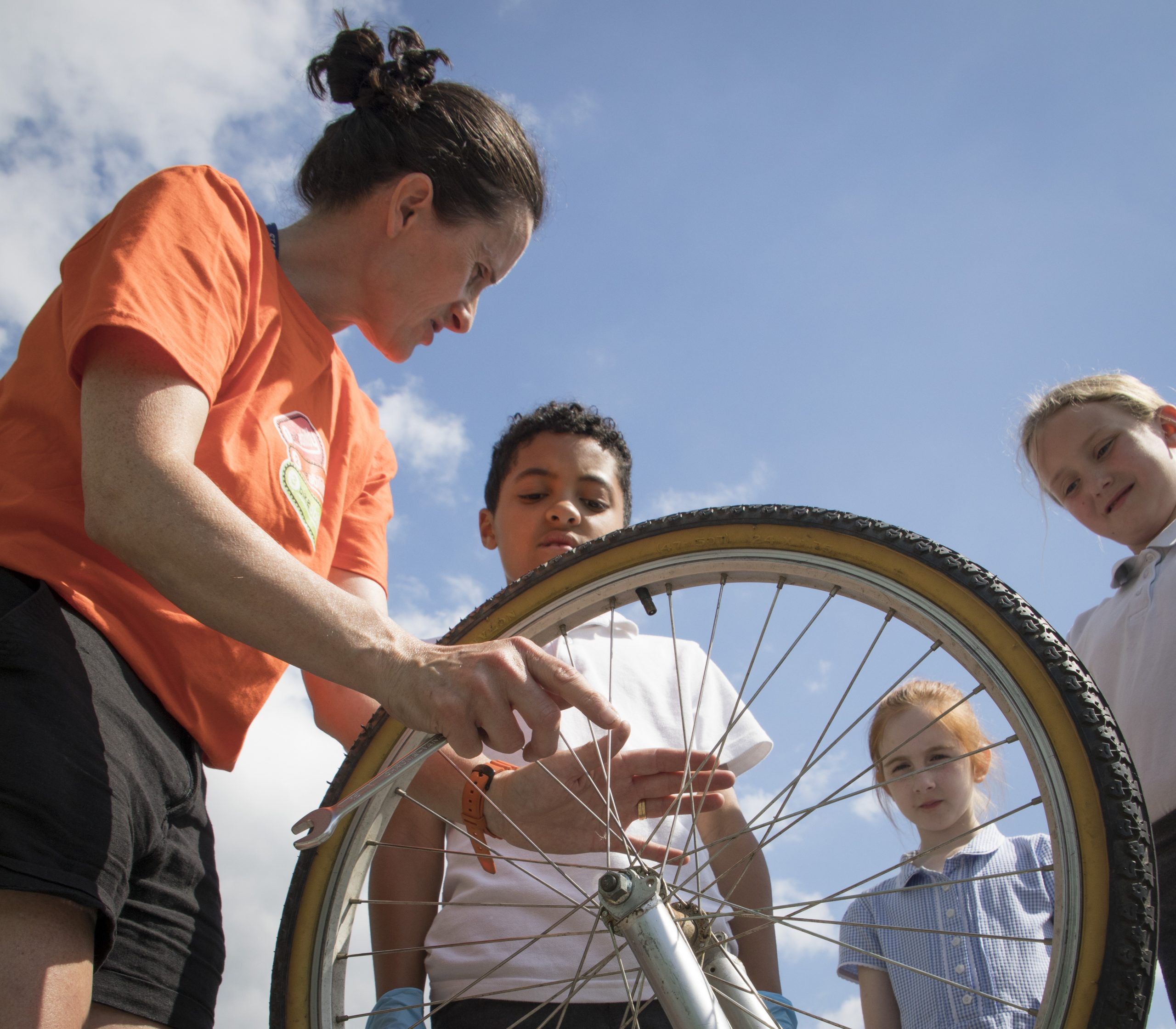 A woman fixes a bike wheel with children looking on