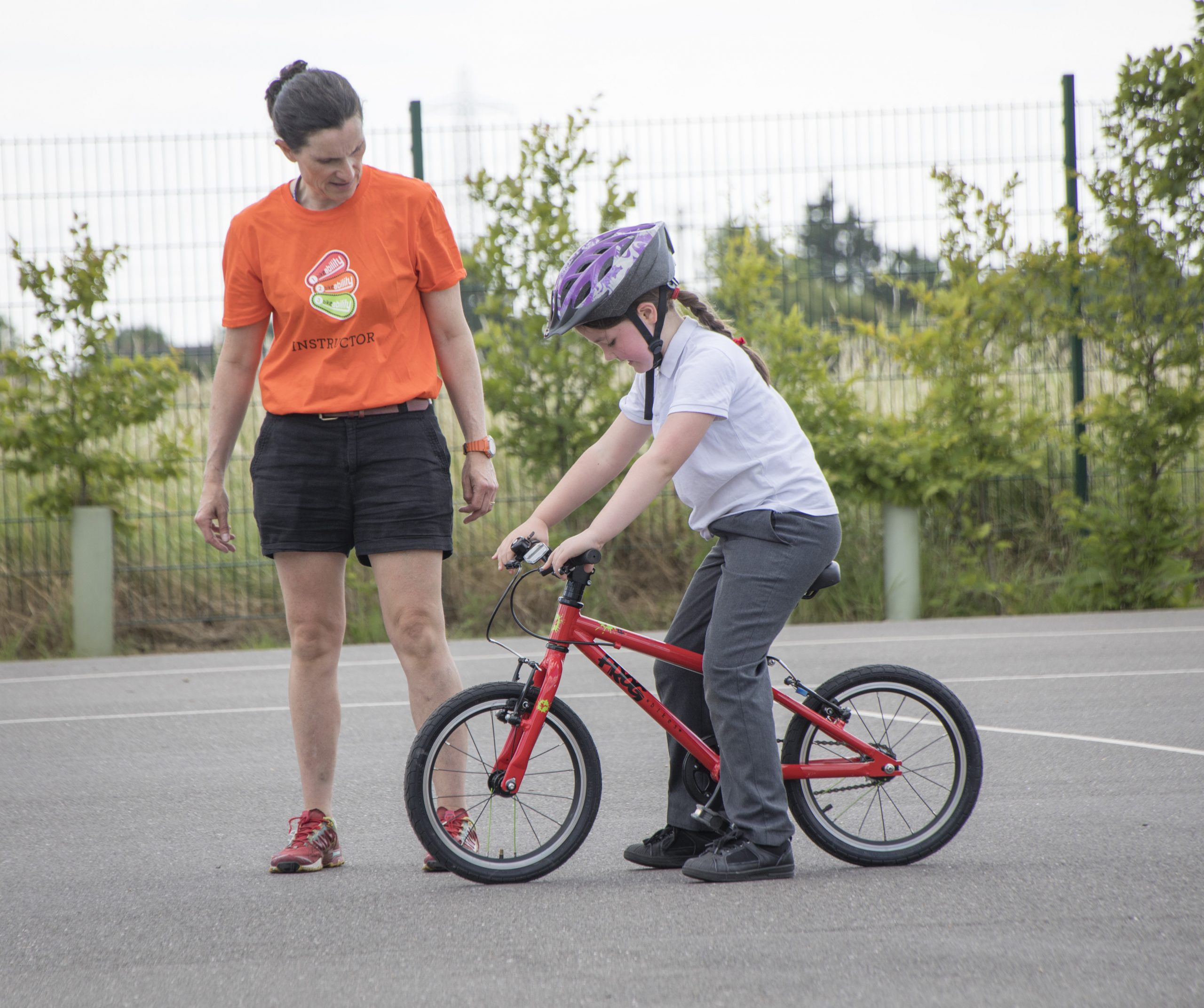 A female Bikeability instructor with a young girl on a bike