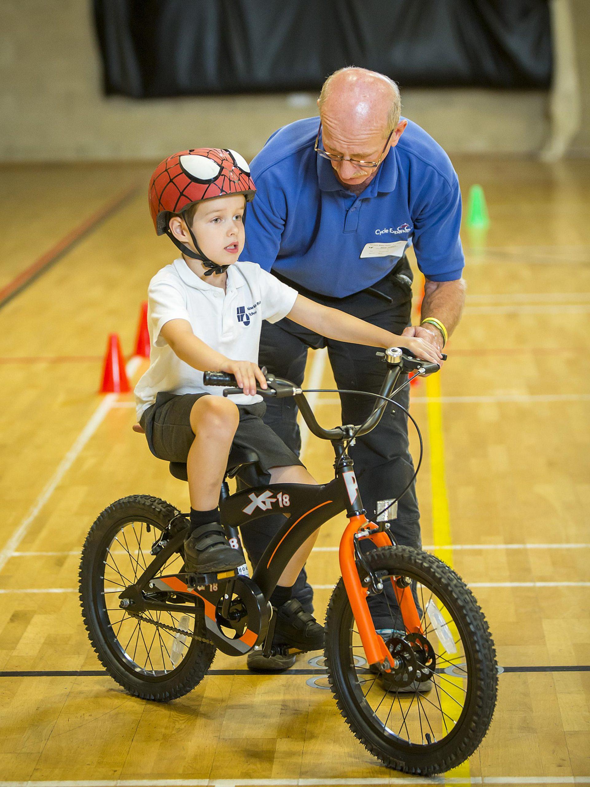 A man teaches a boy how to ride a bike