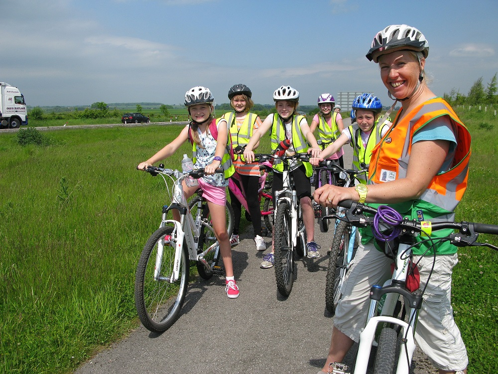 A woman on a bike stands in front of a group of girls on bikes