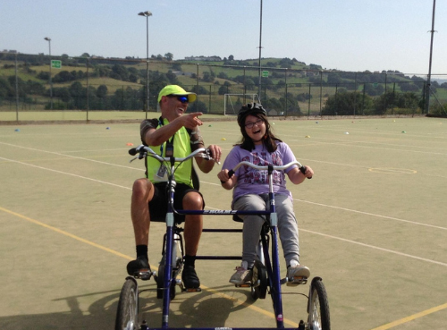 A Bikeability instructor on a side by side bike with a child
